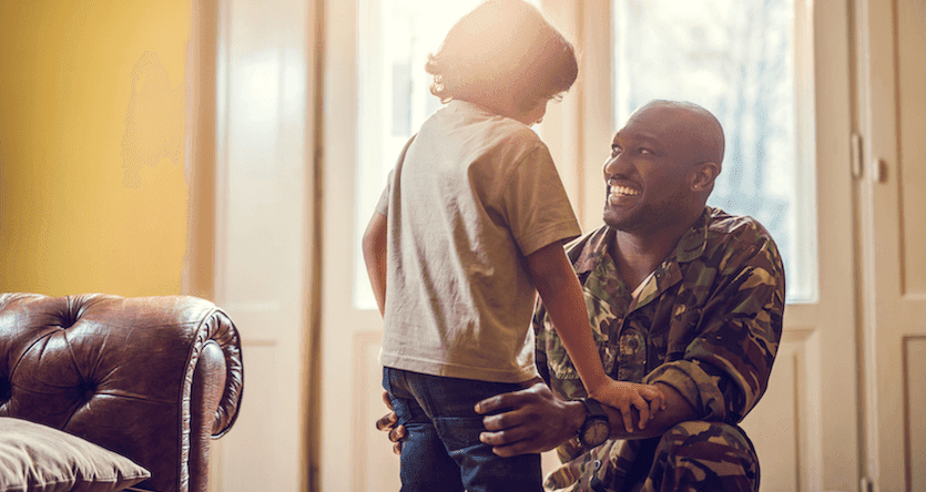 father in military fatigues embracing child