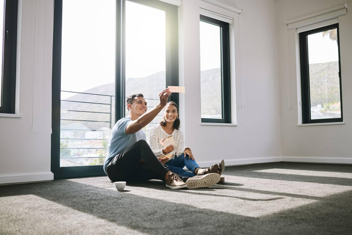 couple sitting on floor in empty room taking a picture in new home