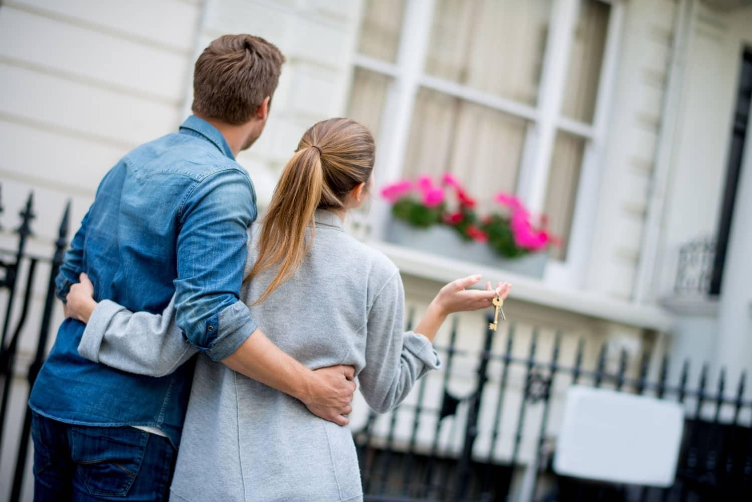 young couple holding keys looking at new home